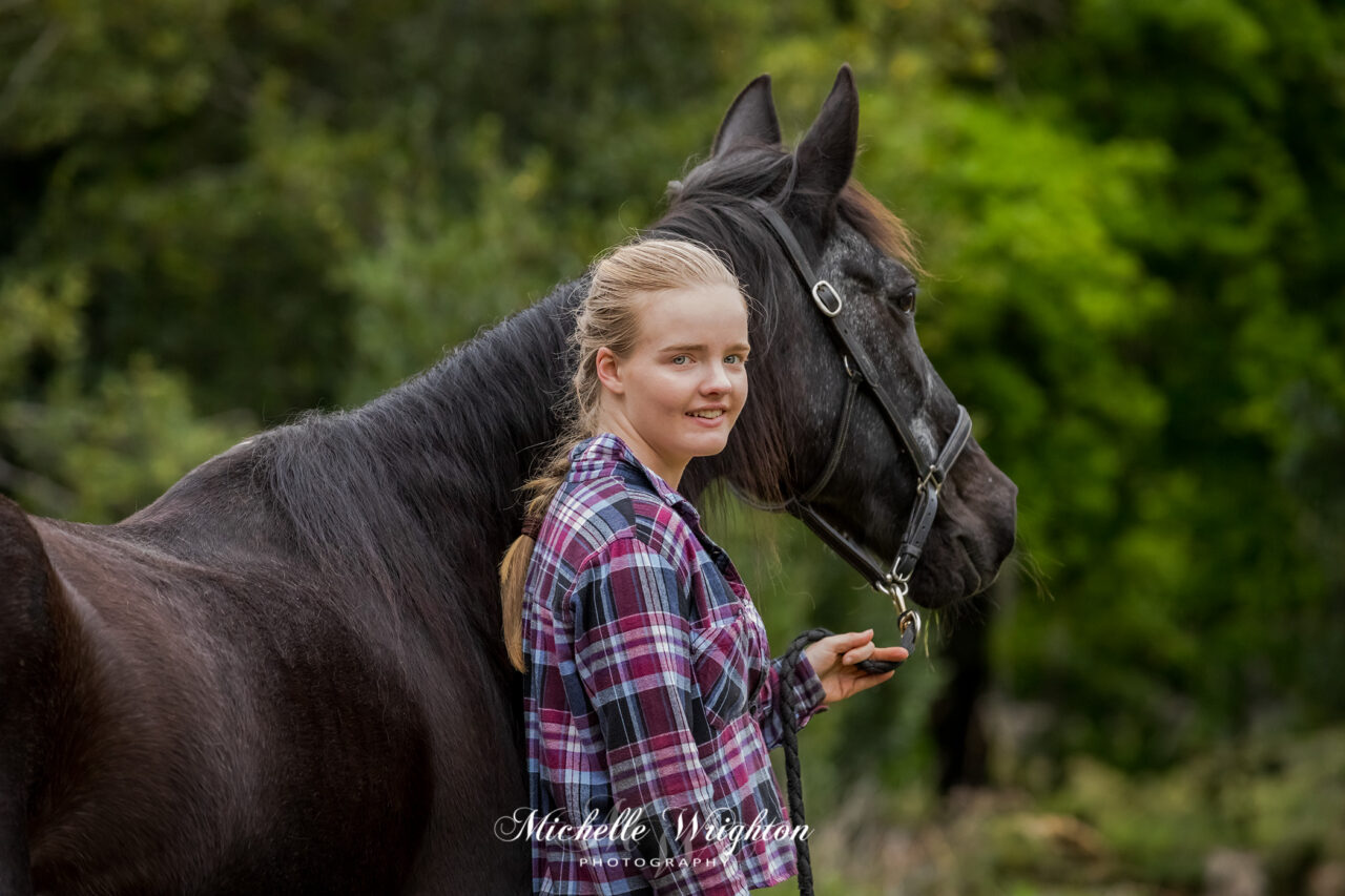 Photograph of a blonde girl and a black horse by professional horse photographer Michelle Wrighton