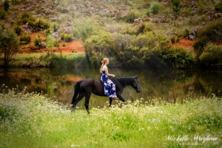 black horse and girl prepare for a photoshoot