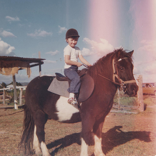 "alt=""Old film photo of the photographer as a young child on a brown and white shetland pony"""